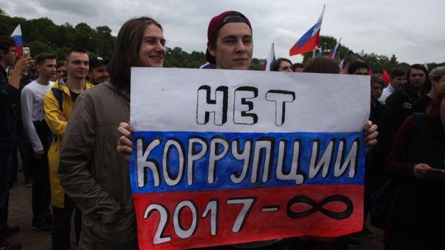 Молодые люди на митинге держат плакат с антикоррупционным призывом