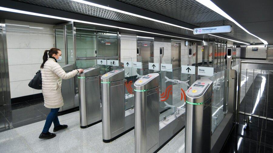 Девушка в маске проходит через турникет в метро