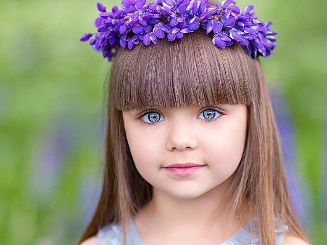 Маленькая девочка в венке из живых фиолетовых цветов