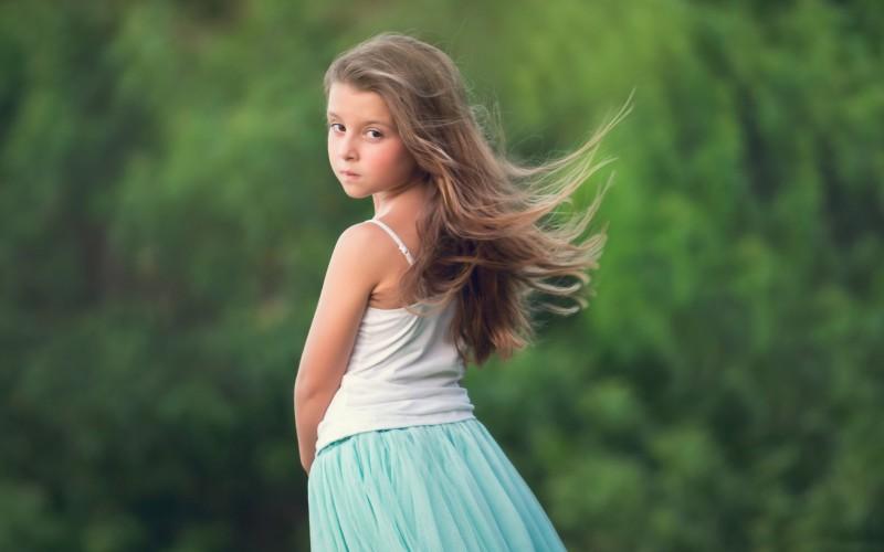 Девочка с развевающимися на ветру волосами смотрит в кадр в полоборота