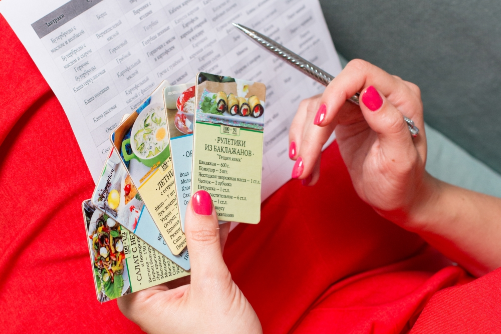 Карточки с рецептами и список с меню в женских руках