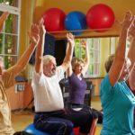 Пожилые люди занимаются на мячах в санатории
