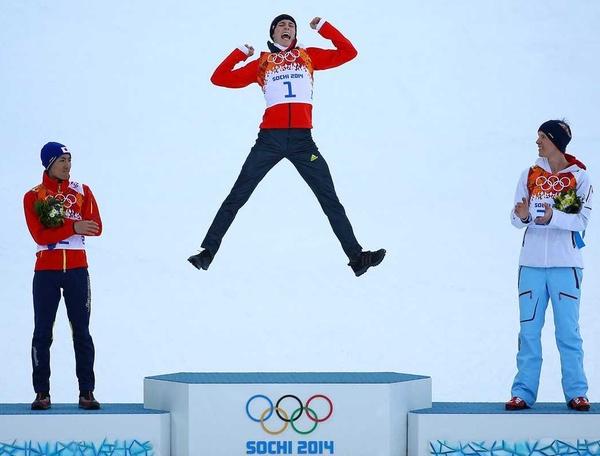 Олимпийский чемпион подпрыгивает на пьедестале