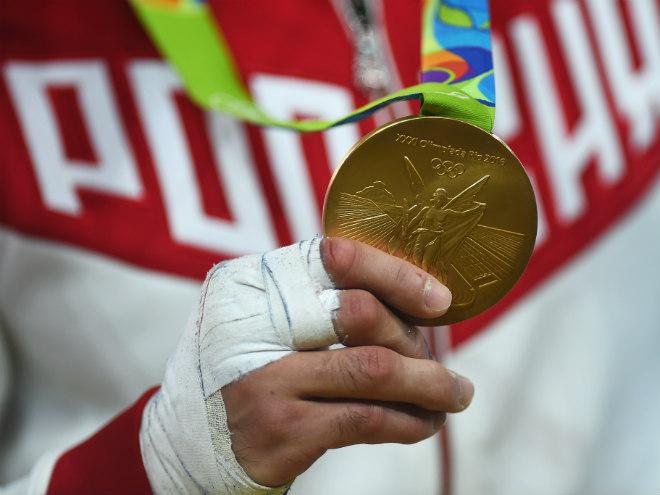 Золотая медаль в перебинтованной руке чемпиона