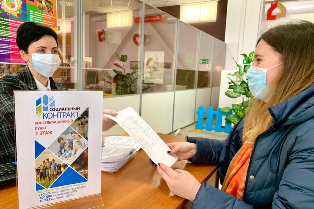 Девушка в маске подает заявление на оформление социального контракта