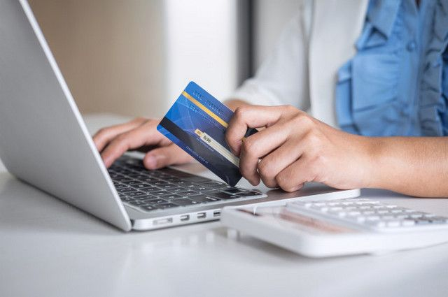 Платежная карта и ноутбук в руках пользователя
