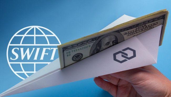 Доллары в бумажном самолетике в руке на фоне значка SWIFT