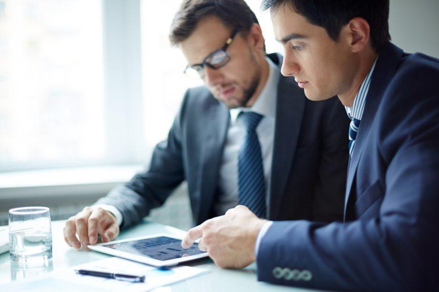 Мужчины изучают информацию на рабочем месте