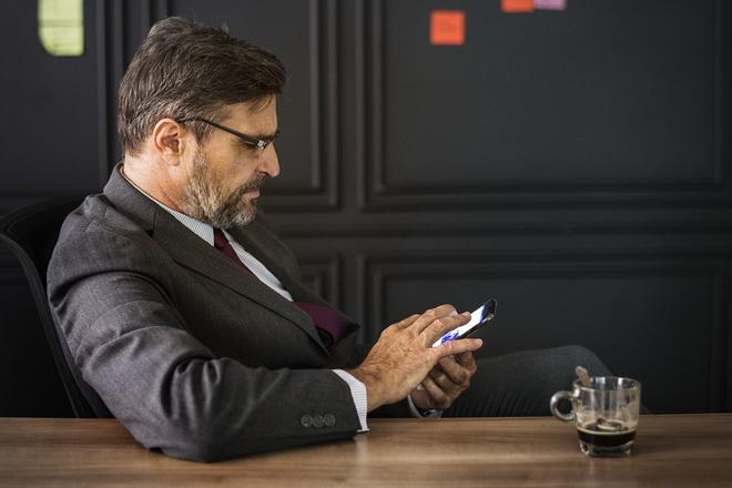 Мужчина в деловом костюме изучает информацию в смартфоне за столом за чашечкой чая