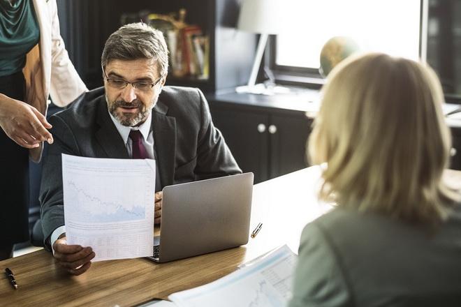 Мужчина в деловом костюме изучает документ в окружении сотрудниц