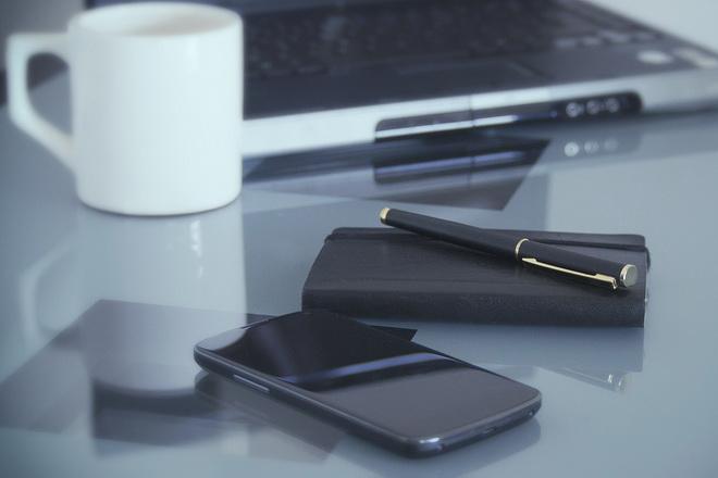 Гаджеты на рабочем столе на фоне чашки