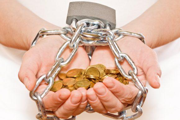 Руки в цепях, удерживающие пригоршню монет