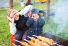 Женщина с ребенком делают очки из рук сидя возле мангала с шашлыками