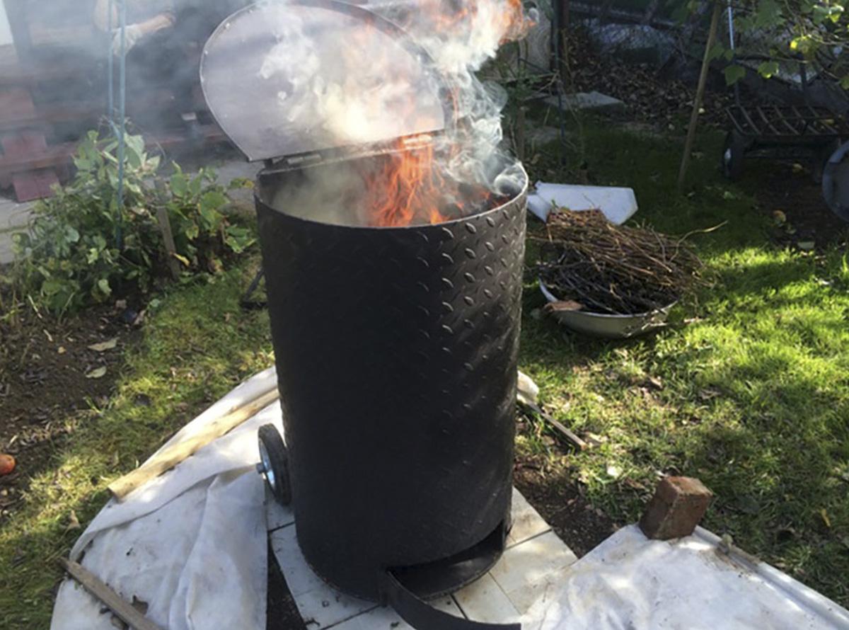 Открытая металлическая бочка с горящим мусором