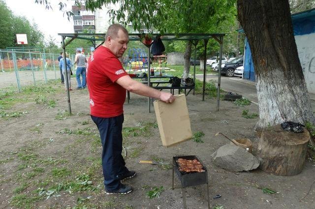 Мужчина во дворе многоквартирного дома раздувает пламя в мангале с шашлыками