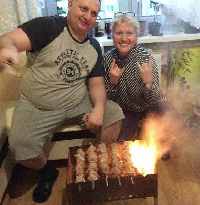 Пара жарит шашлыки на типовой кухне многоквартирного дома