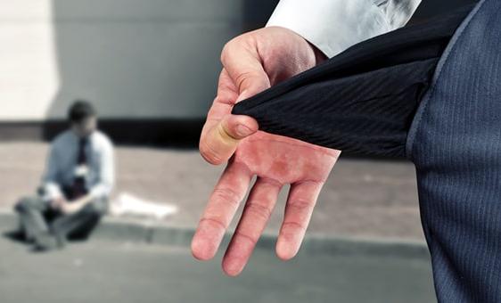 Вывернутый карман брюк на фоне сидящего на тротуаре офисного работника