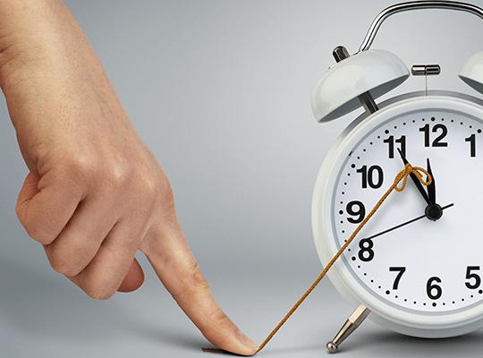 Указательный палец удерживает стрелку будильника с помощью миниатюрной веревки