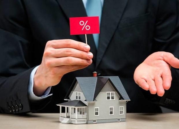 Игрушечный домик и держащий над ним красный флажок с процентами человек в костюме
