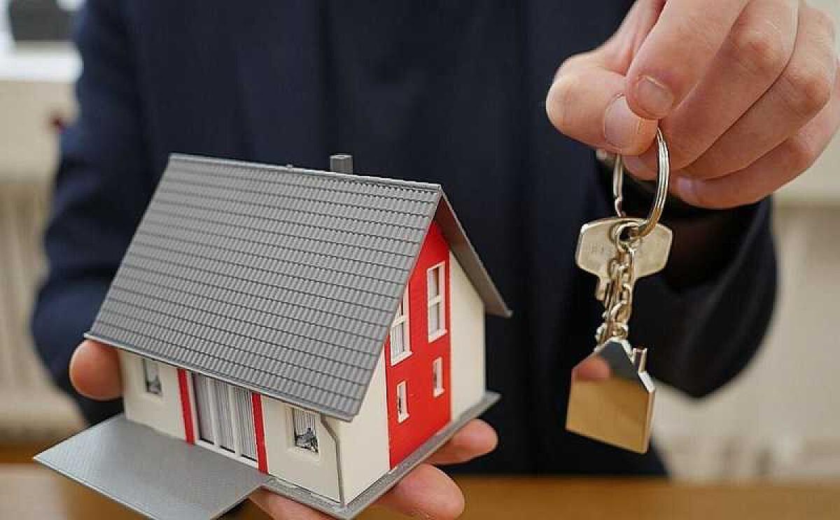 Игрушечный домик в одной руке и ключи в другой