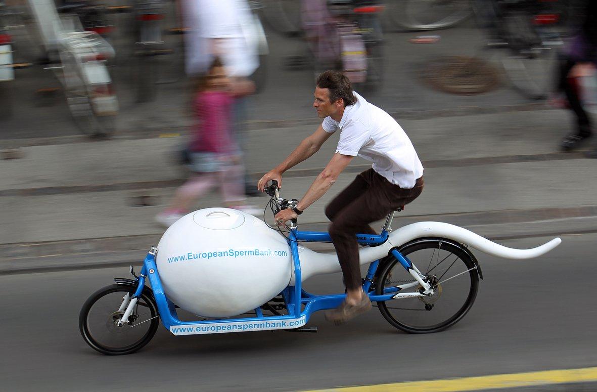 Мужчина едет на электровелосипеде с муляжным сперматозоидом