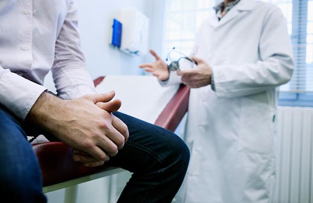 Мужчина в джинсах сидит на кушетке, получая консультацию специалиста