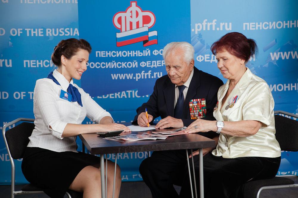 Пожилая пара подписывает договор, предоставляемый сотрудницей пенсионного фонда
