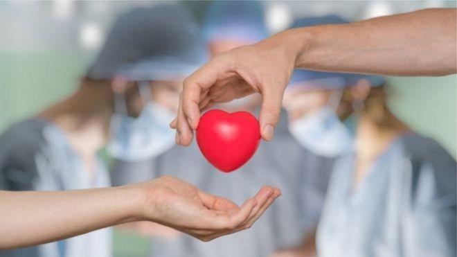 Игрушечное сердце передается из рук в руки на фоне трудящихся в операционной врачей