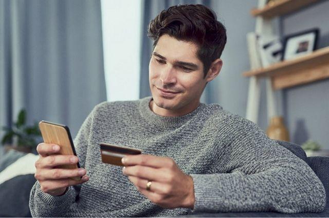 Молодой мужчина держит в руках смартфон и банковскую карту
