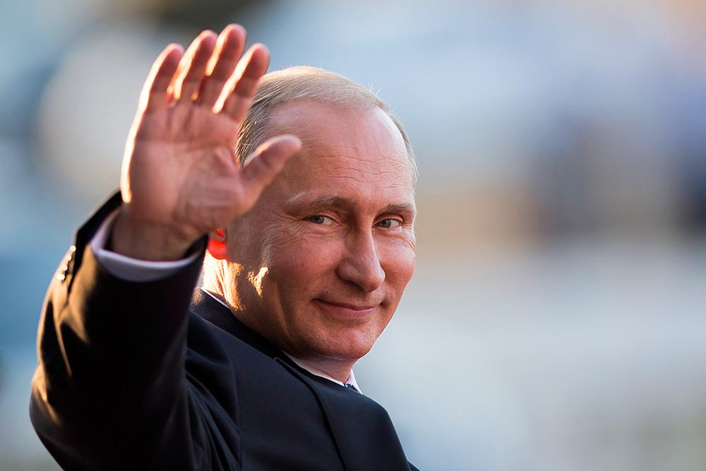 Путин улыбается и машет рукой