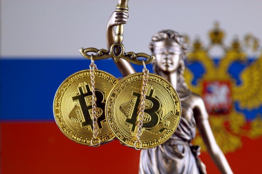 Биткоины на весах Фемиды на фоне российского флага