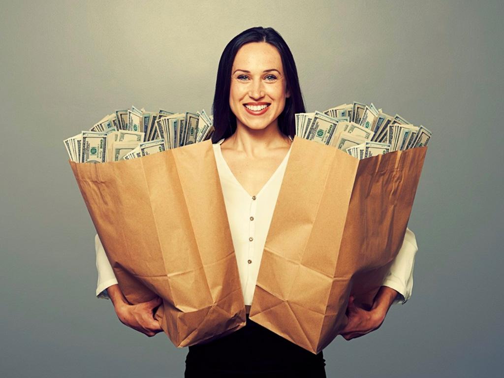 Улыбающаяся женщина с пакетами, наполненными долларами в руках