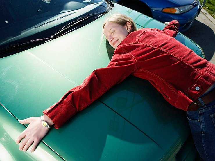 Молодая женщина обнимает авто