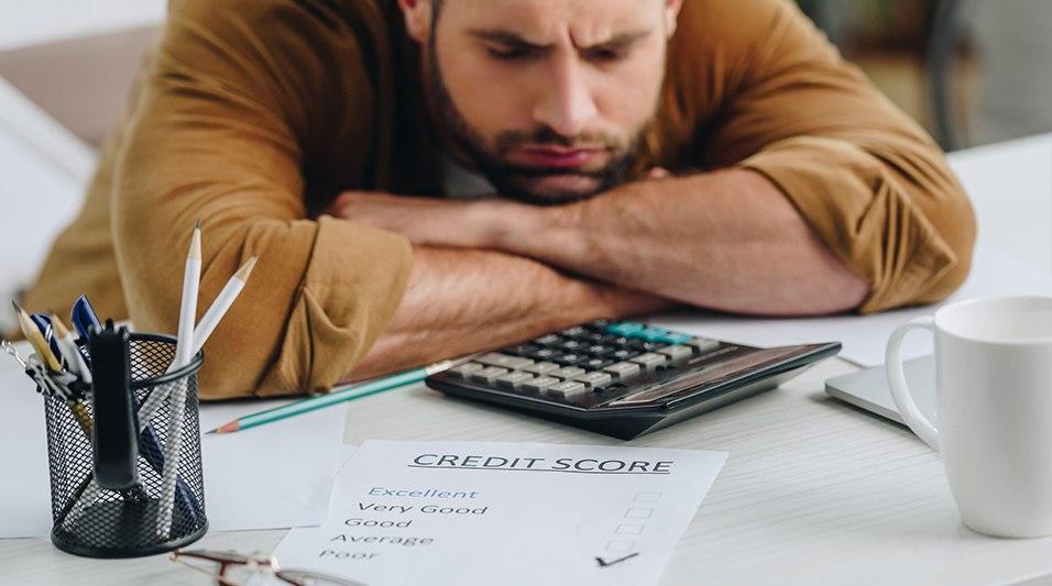 Задумчивый молодой мужчина над калькулятором и кредитной программой