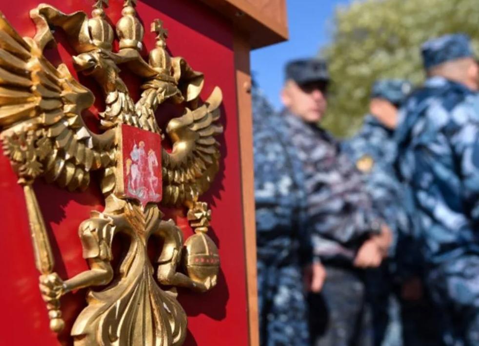 Российский герб и военные на фоне