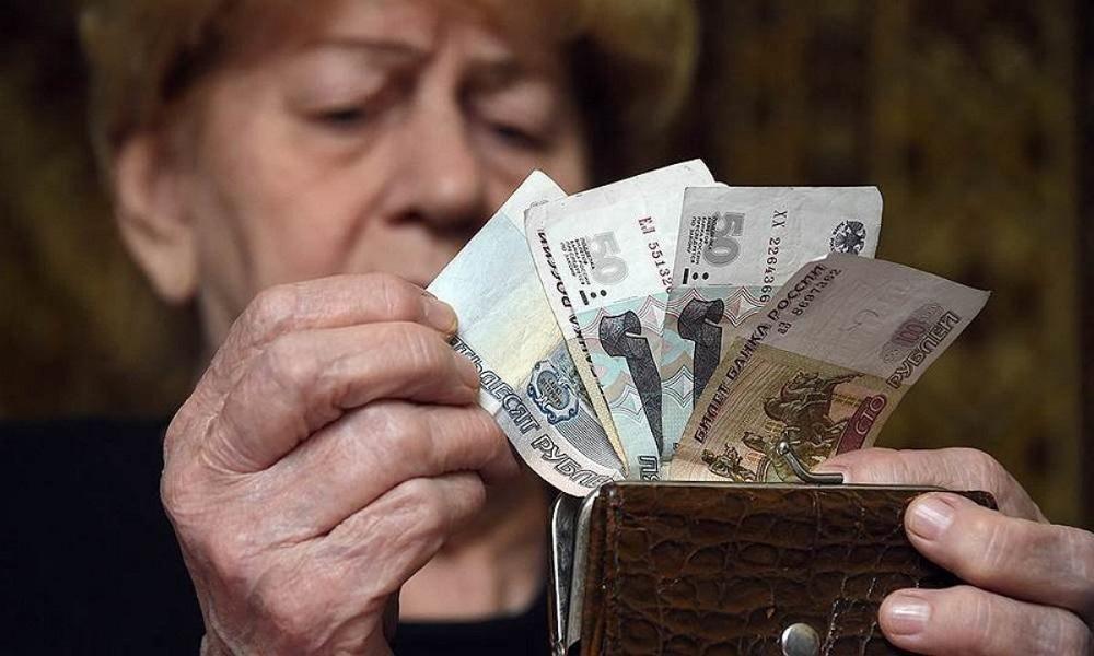 Пожилая женщина пересчитывает рублевые купюры в своем кошельке