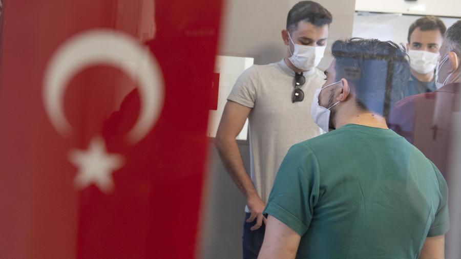 Молодые люди в масках возле турецкого флага