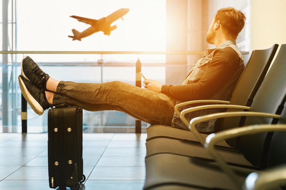 Молодой мужчина в аэропорту смотрит на взлетающий самолет