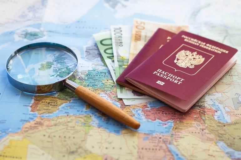 Загранпаспорта, евро и лупа на карте мира