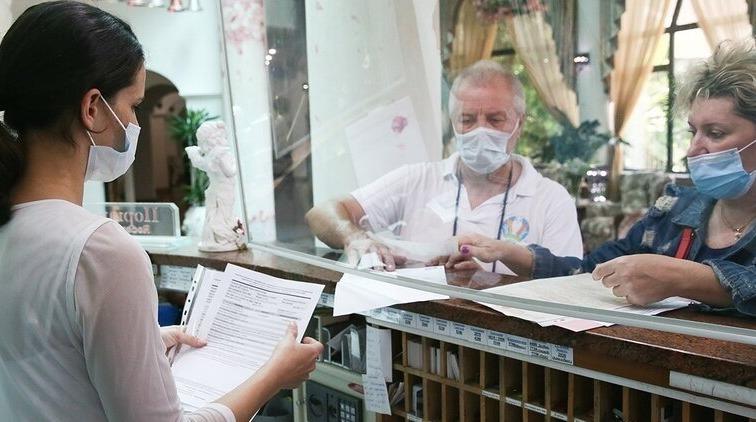 Регистрация на рецепции отеля пожилой пары в масках
