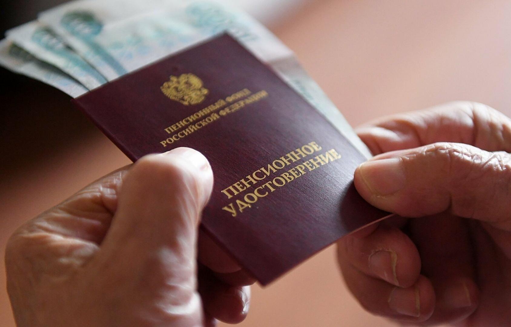 Пенсионное удостоверение с вложенными рублевыми купюрами в руках пенсионера