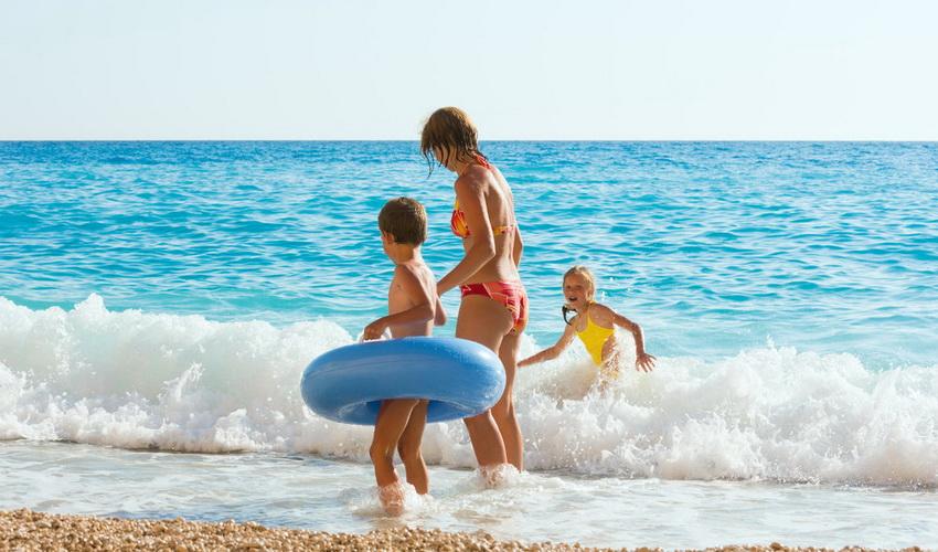 Женщина с детьми купается в море