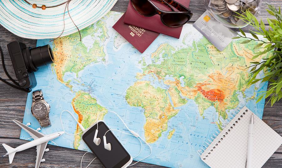 Карта мира, паспорта, фотоаппарат, шляпа, игрушечный самолетик и теоефон