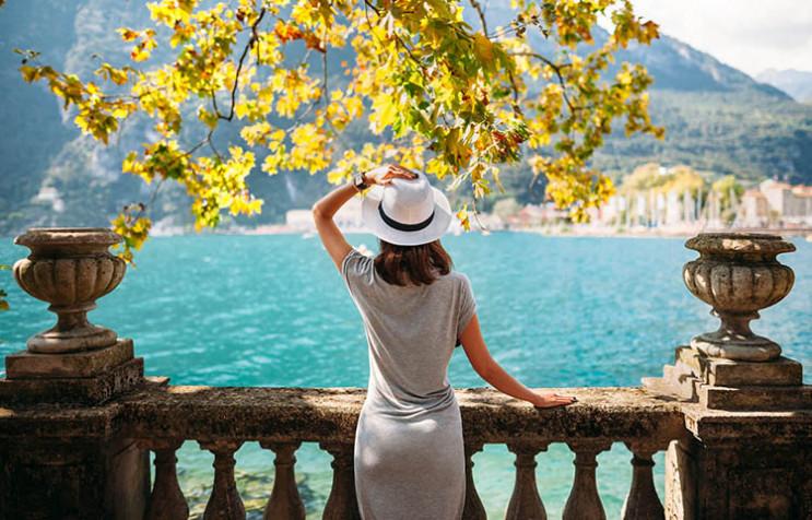Женщина в шляпе смотрит на воду с набережной стоя спиной к объективу