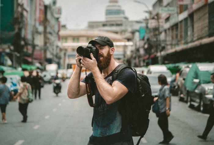 Мужчина снимает на фотоаппарат на улице