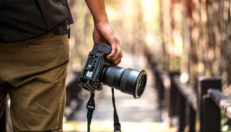 Профессиональная фотокамера в руке