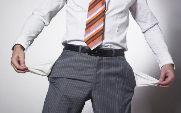 Мужчина держит вывернутые карманы брюк