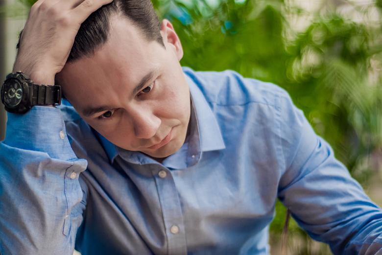 Озадаченный мужчина обхватил голову рукой