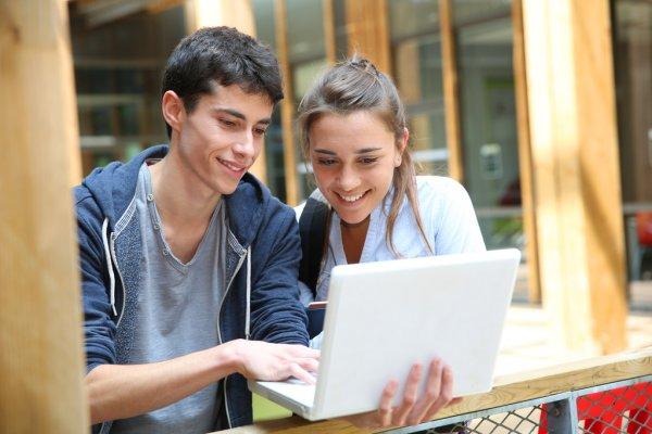 Парень и девушка увлеченно смотрят ноутбук