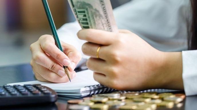 Деньги и карандаш со списком в руках
